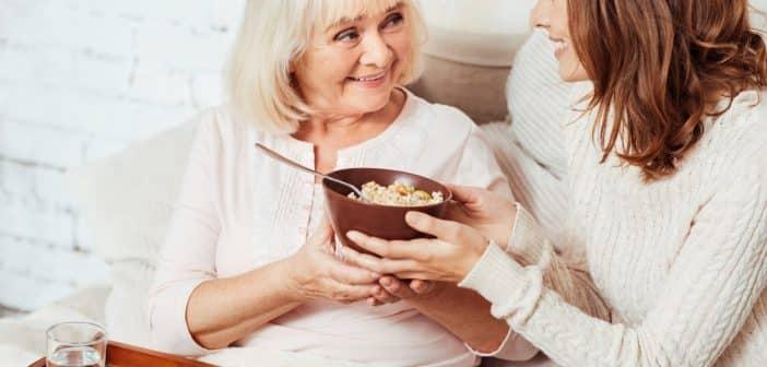 Une femme qui sert une petit déjeuner à une personne agée